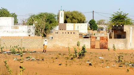 ROAD TO LAMPOUL, SENEGAL - APR 23, 2017: Unidentified Senegalese woman in white shirt and headscarf stands from behind. Still many people in Senegal live in poverty Editorial
