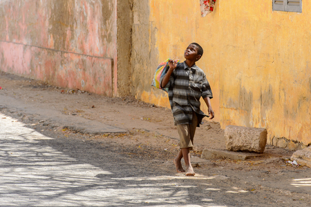 SAINT LOUIS, SENEGAL - APR 24, 2017: Unidentified Senegalese little boy in striped shirt walks with a bag along the road near the building in Saint Louis, one of the biggest cities in Senegal