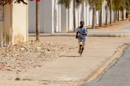SAINT LOUIS, SENEGAL - APR 24, 2017: Unidentified Senegalese little boy runs along the street with palm-trees in Saint Louis, one of the biggest cities in Senegal
