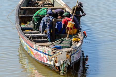 SAINT LOUIS, SENEGAL - APR 24, 2017: Unidentified Senegalese people sail in the boat in the port of Saint Louis, one of the biggest cities in Senegal