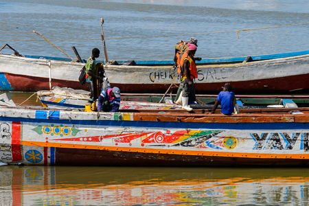 SAINT LOUIS, SENEGAL - APR 24, 2017: Unidentified Senegalese people stand in the boat in the port of Saint Louis, one of the biggest cities in Senegal Editorial