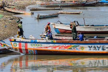 SAINT LOUIS, SENEGAL - APR 24, 2017: Unidentified Senegalese people go on a boat in the port of Saint Louis, one of the biggest cities in Senegal Editorial