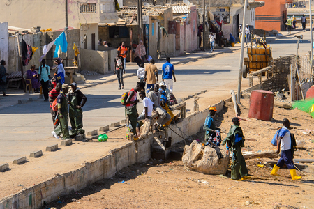 SAINT LOUIS, SENEGAL - APR 24, 2017: Unidentified Senegalese people go down to the beach in the port of Saint Louis, one of the biggest cities in Senegal