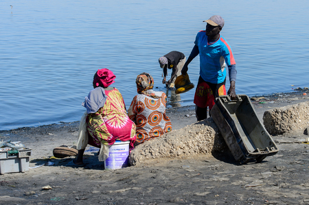 SAINT LOUIS, SENEGAL - APR 24, 2017: Unidentified Senegalese women in colored clothes sit on the buckets in the port of Saint Louis, one of the biggest cities in Senegal Editorial