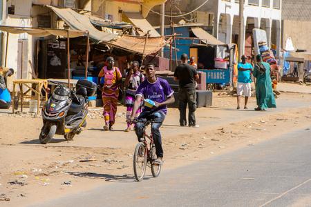 SAINT LOUIS, SENEGAL - APR 24, 2017: Unidentified Senegalese boy rides a bicycle in Saint Louis, one of the biggest cities in Senegal Redakční
