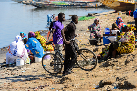 SAINT LOUIS, SENEGAL - APR 24, 2017: Unidentified Senegalese boy pulls his bicycle in the port of Saint Louis, one of the biggest cities in Senegal