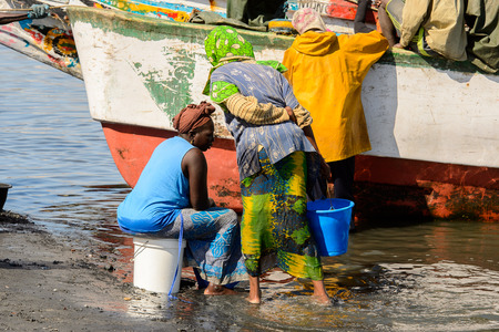SAINT LOUIS, SENEGAL - APR 24, 2017: Unidentified Senegalese woman in blue shirt sits on the bucket near the boat in the port of Saint Louis, one of the biggest cities in Senegal Editorial