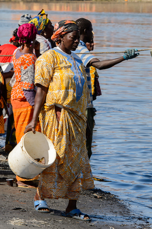 SAINT LOUIS, SENEGAL - APR 24, 2017: Unidentified Senegalese woman carries a bucket in the port of Saint Louis, one of the biggest cities in Senegal Editorial