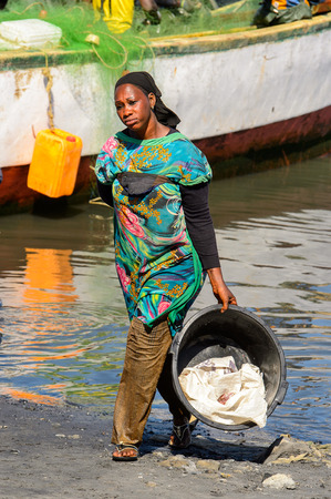 SAINT LOUIS, SENEGAL - APR 24, 2017: Unidentified Senegalese woman carries a basin near the water in the port of Saint Louis, one of the biggest cities in Senegal