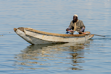 SAINT LOUIS, SENEGAL - APR 24, 2017: Unidentified Senegalese man sails on a boat in the port of Saint Louis, one of the biggest cities in Senegal
