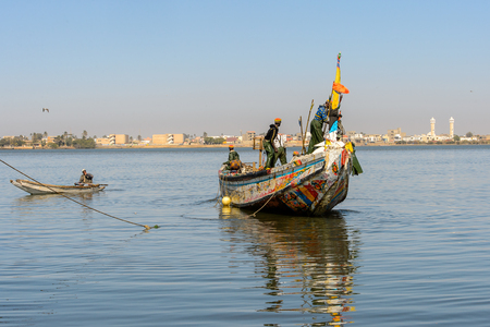 SAINT LOUIS, SENEGAL - APR 24, 2017: Unidentified Senegalese men sail in a boat in the port of Saint Louis, one of the biggest cities in Senegal