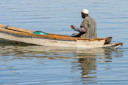 SAINT LOUIS, SENEGAL - APR 24, 2017: Unidentified Senegalese man sails in a boat in the port of Saint Louis, one of the biggest cities in Senegal
