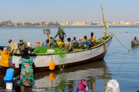 SAINT LOUIS, SENEGAL - APR 24, 2017: Unidentified Senegalese men sail on the boat in the port of Saint Louis, one of the biggest cities in Senegal Editorial
