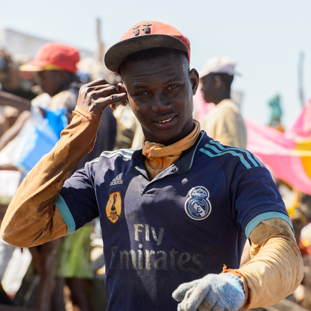 SAINT LOUIS, SENEGAL - APR 24, 2017: Unidentified Senegalese boy in a cap smiles in the port of Saint Louis, one of the biggest cities in Senegal Editorial