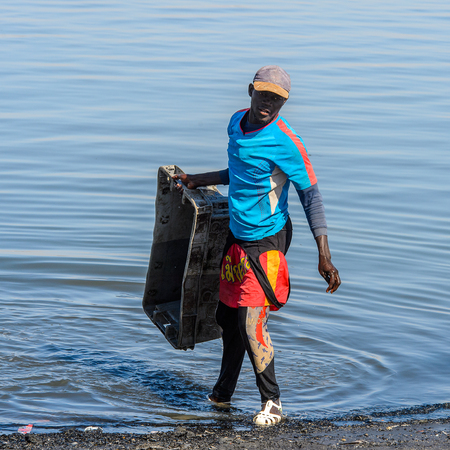 SAINT LOUIS, SENEGAL - APR 24, 2017: Unidentified Senegalese man holds a box near the water in the port of Saint Louis, one of the biggest cities in Senegal