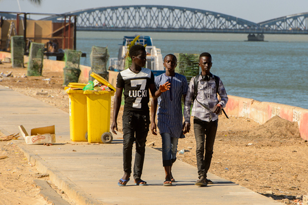 SAINT LOUIS, SENEGAL - APR 24, 2017: Unidentified Senegalese three boys walk along the road on the shore of the ocean in Saint Louis, one of the biggest cities in Senegal