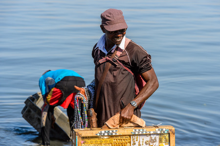 SAINT LOUIS, SENEGAL - APR 24, 2017: Unidentified Senegalese man holds a suitcase and smiles in the port of Saint Louis, one of the biggest cities in Senegal Editorial