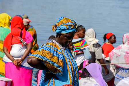 SAINT LOUIS, SENEGAL - APR 24, 2017: Unidentified Senegalese woman in traditional clothes puts her hand on a hip in the port of Saint Louis, one of the biggest cities in Senegal Editorial