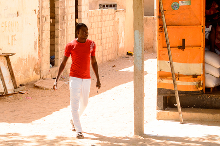 ROAD TO LAMPOUL, SENEGAL - APR 23, 2017: Unidentified Senegalese man in red shirt and white pants walks along the street. Still many people in Senegal live in poverty
