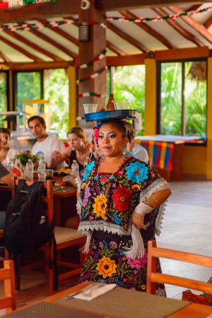 YUCATAN, MEXICO - NOV 4, 2016: Unidentified Mexican woman dances in a restaurant wearing national colthes in a restaruant with a drink over her head. This is one of the way to entertain the tourists