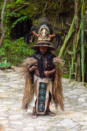 XCARET, MEXICO - NOV 8, 2015: Unidentified man wears a costume of a Maya indian. Maya people are a group of Indigenous people of Mesoamerica