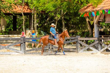 XCARET, MEXICO - NOV 7, 2016: Unidentified cowboy rides a horse in the Xcaret park, Mexico
