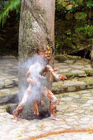XCARET, MEXICO - NOV 8, 2015: Unidentified man wears a costume of a Maya indian and holds a fire in his hand. Maya people are a group of Indigenous people of Mesoamerica