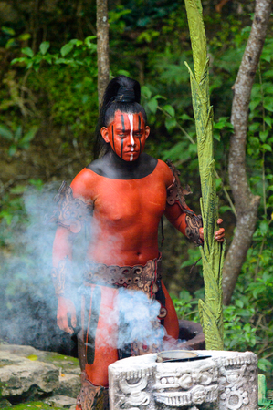 XCARET, MEXICO - NOV 8, 2015: Unidentified man with a red bodypaint as a Maya indian. Maya are a group of Indigenous people of Mesoamerica