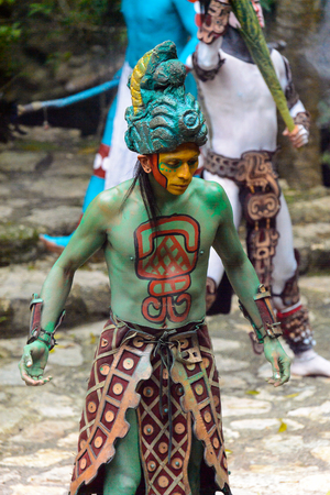 XCARET, MEXICO - NOV 8, 2015: Unidentified man with the green body paint dressed as the Maya indian. The Mayan are a group of Indigenous people of Mesoamerica