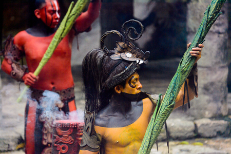 XCARET, MEXICO - NOV 8, 2015: Unidentified man with the red body paint dressed as the Maya indian. The Mayan are a group of Indigenous people of Mesoamerica