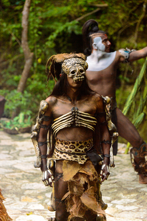 XCARET, MEXICO - NOV 8, 2015: Unidentified man wears a costume with a scull mask of a Maya indian. The Mayan are a group of Indigenous people of Mesoamerica