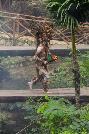 XCARET, MEXICO - NOV 8, 2015: Unidentified man wears a costume of a Maya indian and goes over a bridge. The Mayan are a group of Indigenous people of Mesoamerica