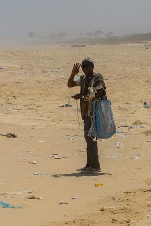 ATL. OCEAN, SENEGAL - APR 27, 2017: Unidentified Senegalese man in sunglasses waves his hand on the coast of the Atlantic Ocean in Senegal