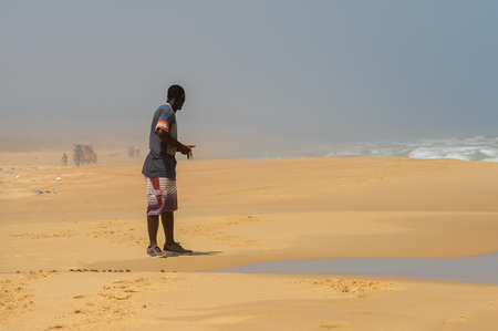 ATL. OCEAN, SENEGAL - APR 27, 2017: Unidentified Senegalese man in colored shirt and shorts stands on the coast of the Atlantic Ocean in Senegal Editorial