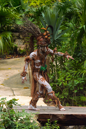 XCARET, MEXICO - NOV 8, 2015: Unidentified man wears a costume of a Maya indian and walks trough the jungle. The Mayan are a group of Indigenous people of Mesoamerica Editorial