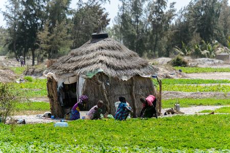 KAYAR, SENEGAL - 27. APRIL 2017: Nicht identifizierte senegalesische Frau und kleine Mädchen sitzen auf dem Boden nahe der Hütte in einem schönen Dorf nahe Kayar, Senegal