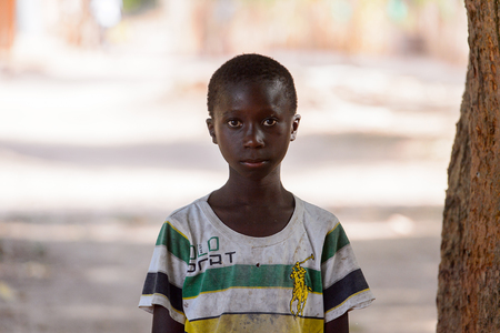 OUSSOUYE, SENEGAL - APR 30, 2017: Unidentified Senegalese  little boy in dirty shirt stands in the Sacred Forest near Kaguit village