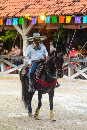 XCARET, MEXICO - NOV 7, 2016: Unidentified Mexican cowboy rides a horse and shows tricks  in the Xcaret park, Mexioc 新闻类图片