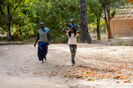 OUSSOUYE, SENEGAL - APR 30, 2017: Unidentified Senegalese  man carries a baby boy on his shoulders in the Sacred Forest near Kaguit village Editorial