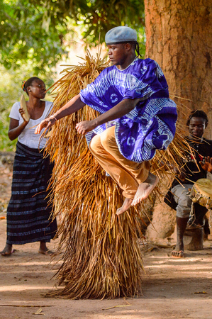 Kaguit vil., SENEGAL - APR 30, 2017: Unidentified Diola man in a dress jumps during a traditional dance Kumpo in a Sacred Forest near Kaguit village Zdjęcie Seryjne - 105702895