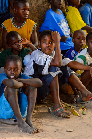 OUSSOUYE, SENEGAL - APR 30, 2017: Unidentified Senegalese group of little boys sit on the ground and watch the show in the Sacred Forest near Kaguit village