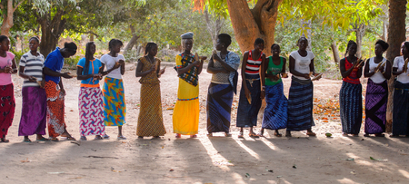 Kaguit vil., SENEGAL - APR 30, 2017: Unidentified Diola women in colored clothes hold a special attributes during a traditional dance Kumpo in a Sacred Forest near Kaguit village