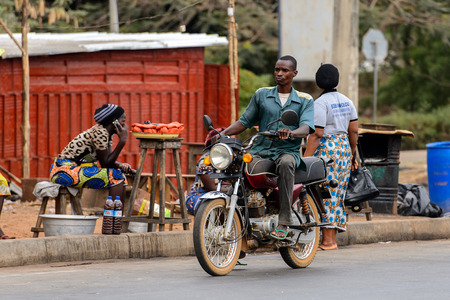 PIRA, BENIN - JAN 12, 2017: Unidentified Beninese man rides a motorcycle and looks around. Benin people suffer of poverty due to the bad economy.