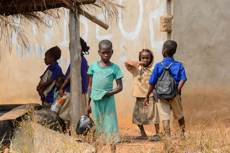PIRA, BENIN - JAN 12, 2017: Unidentified Beninese little children walk on the street. Benin children suffer of poverty due to the bad economy.