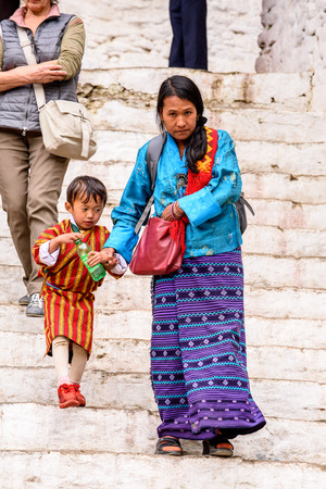 TRIMPHU, BHUTAN - MAR 8, 2017: Unidentified Ngalops woman in traditional clothes walks on the street with a little boy. Ngalops is one of the most populous ethnic groups of Bhutan Editorial