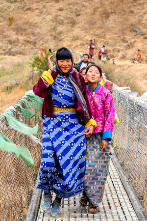 TRIMPHU, BHUTAN - MAR 8, 2017: Unidentified Ngalops girls in traditional clothes walk along the bridge. Ngalops is one of the most populous ethnic groups of Bhutan Editorial