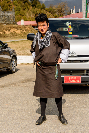 TRIMPHU, BHUTAN - MAR 8, 2017: Unidentified Ngalops boy in traditional clothes stands in front of the car. Ngalops is one of the most populous ethnic groups of Bhutan