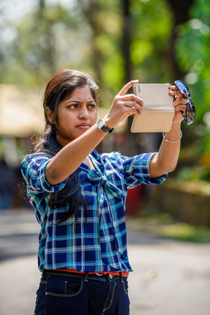 SIKKIM, INDIA - MAR 13, 2017: Unidentified Indian girl with pony tail in plaid shirt tries to take a picture on her cellphone.