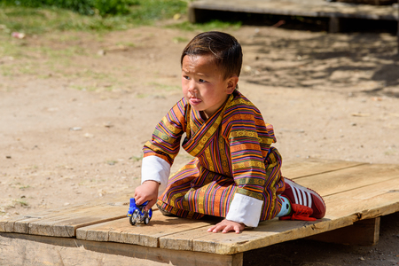 TRIMPHU, BHUTAN - MAR 8, 2017: Unidentified Ngalops little boy plays with a tiny motorcycle. Ngalops is one of the most populous ethnic groups of Bhutan Éditoriale