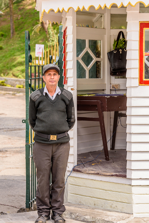SIKKIM, INDIA - MAR 13, 2017: Unidentified Indian guardian in uniform stands near postoffice and gates.